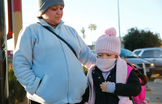 Maxi Cortes and her daughter, Jasmine Cortes, 7, try to stay warm on their way to Horace Mann Elementary School in San Jose, California, on Tuesday, Dec. 5, 2017. Near freezing temperatures are expected overnight. (Gary Reyes/ Bay Area News Group)
