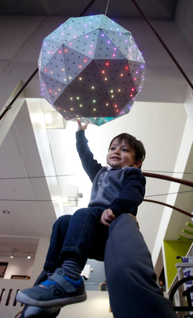 Two-year-old Viibhuraj Kasliwal is hoisted by his father Vishal Kasliwal for a better look at the Times Square-styled New Year's Eve ball that descended at the Children's Discovery Museum of San Jose, Sunday, Dec. 31, 2017, in San Jose, Calif. (Karl Mondon/Bay Area News Group)