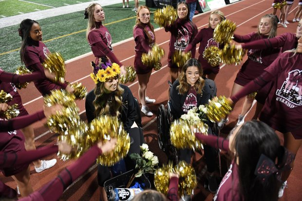 Gianna Baca, left center, and her twin sister, Natalia Baca, right center,are surrounded by fellow cheerleaders as they attend a homecoming football game at Faith Lutheran Middle School and High School on Oct. 6. Natalia and Gianna were both shot by suspected gunman, Stephen Paddock while attending the Route 91 Harvest Festival. MUST CREDIT: Washington Post photo by Matt McClain