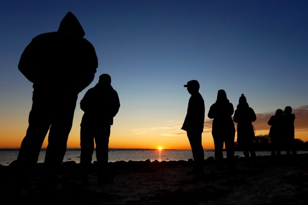 People gather to watch the sunrise on West Island in Fairhaven, Mass., on Thursday, Dec. 21, 2017 during a Winter Stolstice Sunrise Stroll hosted by the Buzzards Bay Coalition. (Peter Pereira/Standard Times via AP)