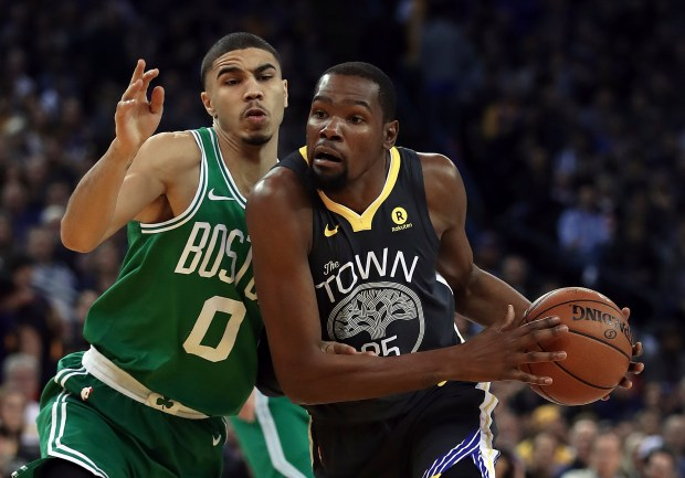 Golden State Warriors' Kevin Durant, right, drives the ball against Boston Celtics' Jayson Tatum (0) during the first half of an NBA basketball game Saturday, Jan. 27, 2018, in Oakland, Calif. (AP Photo/Ben Margot)