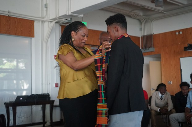 Alicia Dixon, executive director of Marcus Foster Education Institute, lead agency of the College Bound Brotherhood, awards a graduate a kente cloth stole in recognition of his graduation achievement and matriculation to college at the College Bound Brotherhood graduation ceremony at Merritt College. (Photo by Pendarvis Harshaw, courtesy of College Bound Brotherhood program)