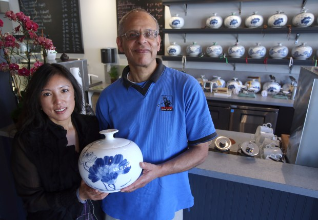 Co-owners John Brown, right, and Xiaobei Wei, are photographed with a canister of Chinese tea at Sophie's Cuppa Tea in the Montclair district of Oakland, Calif. on Friday, Aug. 1, 2014. They specialize in imported teas from China, and also serve pastries and Tara's Organic Ice Cream. (Jane Tyska/Bay Area News Group)