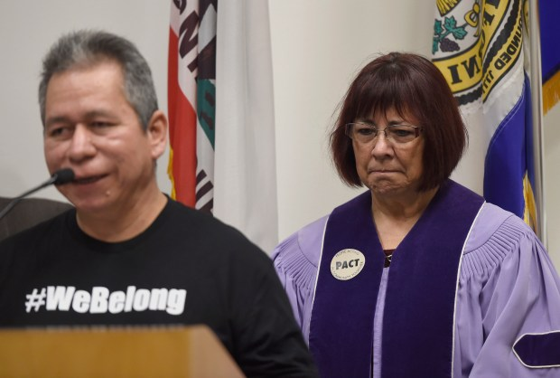 Liliana Devalle, pastor at Grace Baptist Church, listens as Ernesto Perez, PACT leader, Our Lady of Guadalupe, speak during a press conference at San Jose City Hall in San Jose, Calif., on Wednesday, Jan. 24, 2018. City officials, local community leaders and members of People Acting in Community Together (PACT) discussed the resources and services available to undocumented immigrants amid rumors of impending ICE raids. (Dan Honda/Bay Area News Group)
