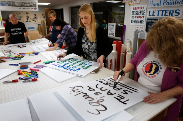 Heather Valentine, center, of San Jose, Colleen Pizarev, right, of San Jose, and others make signs at West Mountain Sign in San Jose, California, Thursday, Jan. 11, 2018. Bay area women are gearing up for the next Women's March nation-wide on January 20, 2018. They were creating the signs they'll carry in the San Jose march next Saturday. (Patrick Tehan/Bay Area News Group)