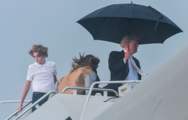 US President Donald Trump holds an umbrella as he waits for his son Barron and wife Melania to board Air Force One at Palm Beach International Airport in West Palm Beach, Florida. (Photo credit should read NICHOLAS KAMM/AFP/Getty Images)