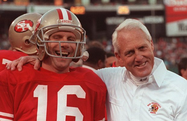 San Francisco 49ers quarterback Joe Montana and head coach BIll Walsh smile for photographers during the closing moments of their playoff game against the Minnesota Vikings on Jan. 4, 1989 at Candlestick Park. (AP Photo)