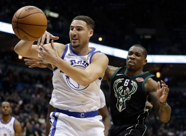 Golden State Warriors' Klay Thompson grabs a rebounds in front of Milwaukee Bucks' Eric Bledsoe during the second half of an NBA basketball game Friday, Jan. 12, 2018, in Milwaukee. The Warriors won 108-94. (AP Photo/Morry Gash)