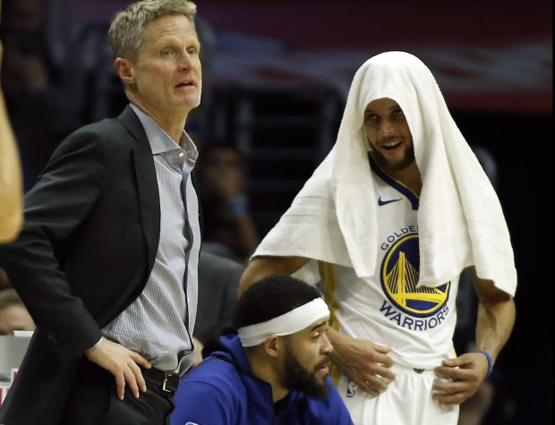 Golden State Warriors guard Stephen Curry, right, mirrors head coach head coach Steve Kerr, left, with center JaVale McGee between them, during the second half of an NBA basketball game against the Los Angeles Clippers in Los Angeles, Saturday, Jan. 6, 2018. The Warriors won 121-105.(AP Photo/Alex Gallardo)