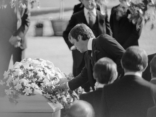 Actor Robert Wagner reaches for a flower off the bouquet-draped casket of his wife Natalie Wood, during services Wednesday, Dec. 3, 1981 at Westwood Memorial Park. The 43 year old actress was an apparent drowning victim off the coast of Santa Cataline Island over the weekend. (AP Photo/Reed Saxon)