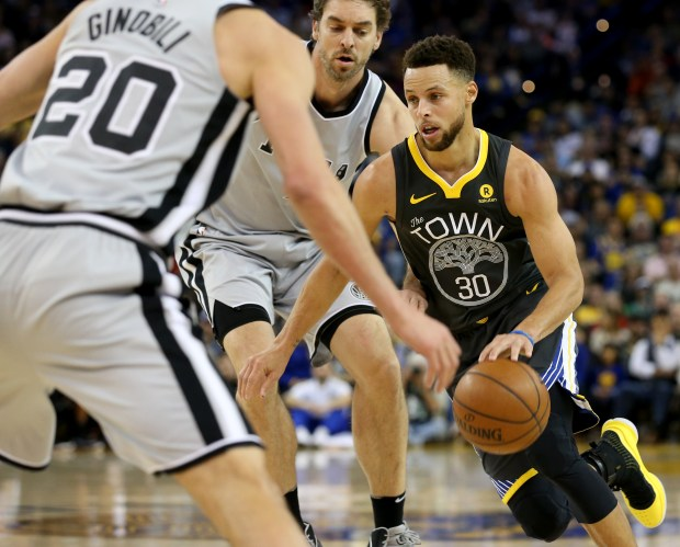 Golden State Warriors' Stephen Curry (30) dribbles through San Antonio Spurs' Manu Ginobili (20) and Pau Gasol (16) in the fourth period of a NBA game at Oracle Arena in Oakland, Calif., on Saturday, Feb. 10, 2018. (Anda Chu/Bay Area News Group)