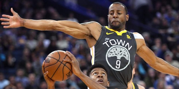 Golden State Warriors' Andre Iguodala (9) blocks Los Angeles Clippers' Tyrone Wallace (12) in the fourth period of their NBA game at Oracle Arena in Oakland, Calif., on Thursday, Feb. 22, 2018. (Doug Duran/Bay Area News Group)