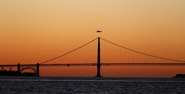 A helicopter hoovers along the Golden Gate bridge at dusk seen from Treasure Island in San Francisco, Calif., on Tuesday, Feb. 13, 2018. Since there is no rain coming soon, February could become the first dry month in more than 150 years with no rainfall, according to the National Weather Service. (Ray Chavez/Bay Area News Group)