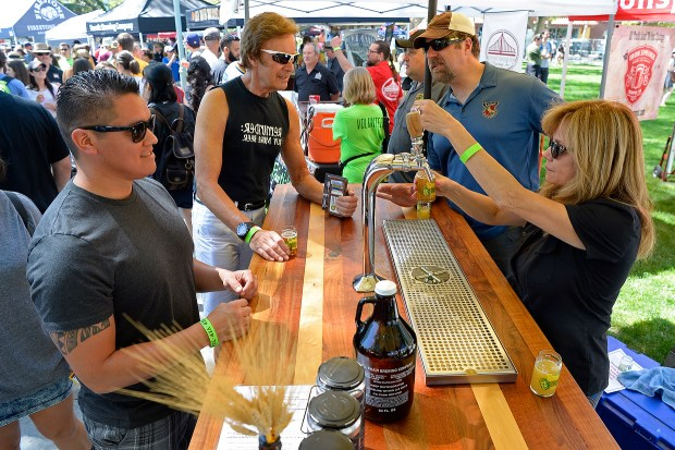 Nati Porras, of Antioch, waits for a glass of Fourth Bore IPA from E.J. Phair from Becky Wynn, of Pittsburg, while attending the 8th annual Spring Brews Festival at Todos Santos Plaza in Concord, Calif. on Saturday, April 1, 2017. (Jose Carlos Fajardo/Bay Area News Group)