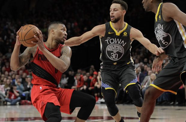Portland Trail Blazers guard Damian Lillard, left, looks to pass the ball as Golden State Warriors guard Stephen Curry defends during the second half of an NBA basketball game in Portland, Ore., Wednesday, Feb. 14, 2018. The Trail Blazers won 123-117. (AP Photo/Steve Dipaola)