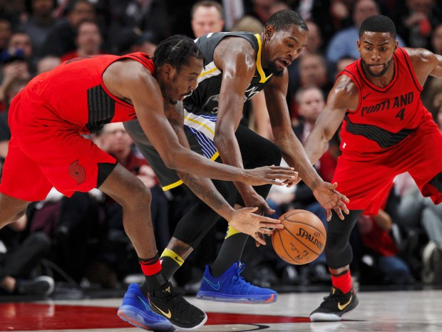 Golden State Warriors forward Kevin Durant, center, vies for a loose ball with Portland Trail Blazers forwards Al-Farouq Aminu, left, and Maurice Harkless during the second half of an NBA basketball game in Portland, Ore., Wednesday, Feb. 14, 2018. The Trail Blazers won 123-117.(AP Photo/Steve Dipaola)
