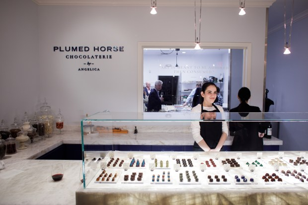 Plumed Horse Chocolaterie's employee Kiri Wanless greets guests during the store's grand opening on Feb. 1, 2018 in Saratoga. Most of the chocolates are hand painted by a chocolatier, Angelica Duarte. (Dai Sugano/Bay Area News Group)