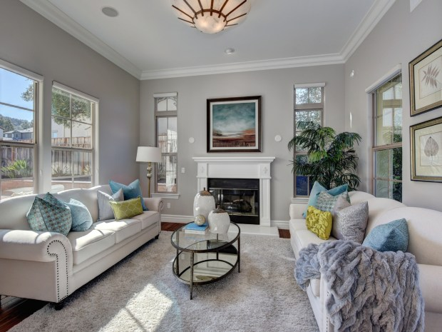 The light and bright formal living room includes a lovely fireplace and a view of the courtyard.