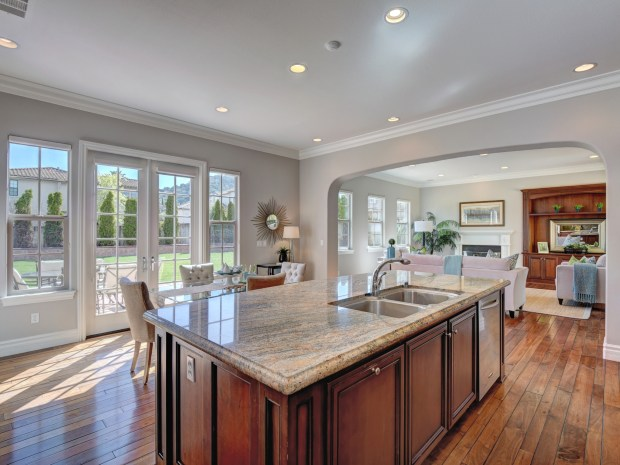 The eat-in kitchen features granite counters and island, cherrywood cabinetry, double ovens and a six-burner cooktop.