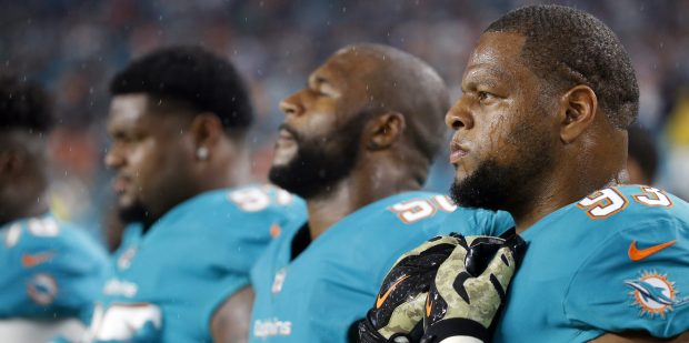 Miami Dolphins defensive tackle Ndamukong Suh (93), stands for the pre-game ceremony at an NFL football game against the Oakland Raiders, Sunday, Nov. 5, 2017, in Miami Gardens, Fla. (AP Photo/Wilfredo Lee)