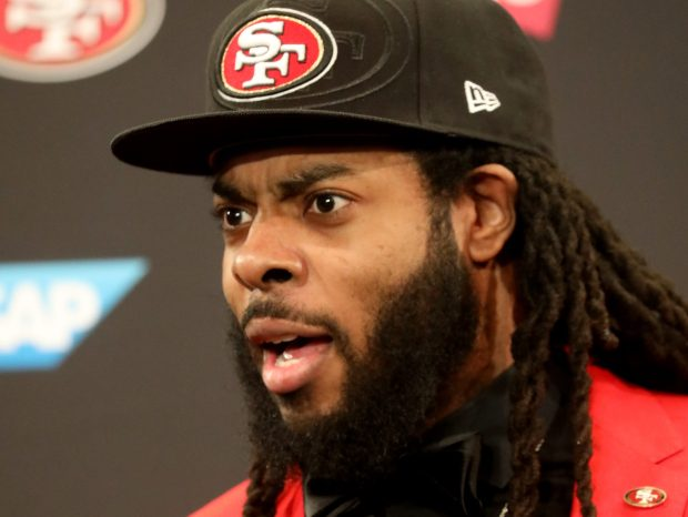 Former Seattle Seahawk Richard Sherman, wearing a bright red suit, meets the press Tuesday, March 20, 2018, at the San Francisco 49ers headquarters in Santa Clara, Calif. Sherman recently signed a contract to play with San Francisco. (Karl Mondon/Bay Area News Group)