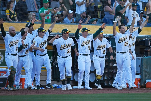 The Oakland Athletics celebrate in the dugout as teammate Marcus Semien (10) connects for the game winning RBI single to defeat the Los Angeles Angels in the 11th inning of their opening day MLB game at the Oakland Coliseum in Oakland, Calif., on Thursday, March 29, 2018. The Oakland Athletics defeated the Los Angeles Angels 6-5 in eleven innings. (Jose Carlos Fajardo/Bay Area News Group)