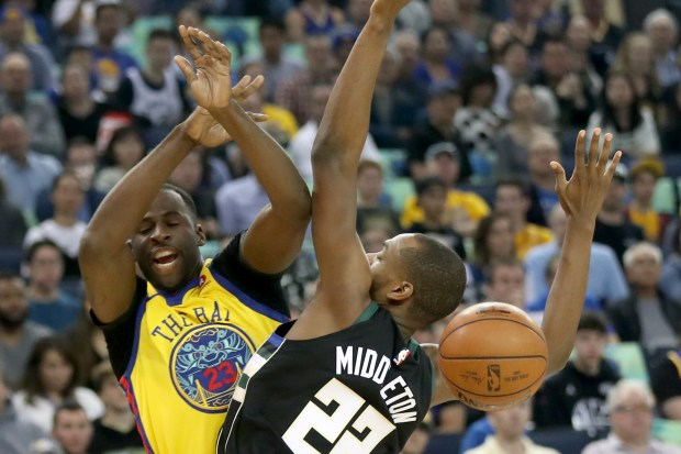 Draymond Green of the Golden State Warriors (23) losses control over the ball under pressure from Milwaukee Bucks Khris Middleton (22) in the first half of an NBA game at the Oracle Arena in Oakland, California, on Thursday, March 29, 2018 (Ray Chavez / Bay Area Newsgroup)
