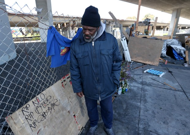 "Marcus Emery, who is homeless, looks at a sign in memory of his friend Dominic ""Boobie"" Jarvis at an encampment on Sycamore Street in Oakland, Calif., on Wednesday, March 22, 2018. Jarvis was shot and killed at the camp on Sept. 5, 2017. Emery had known Jarvis for 30 years. (Jane Tyska/Bay Area News Group)"