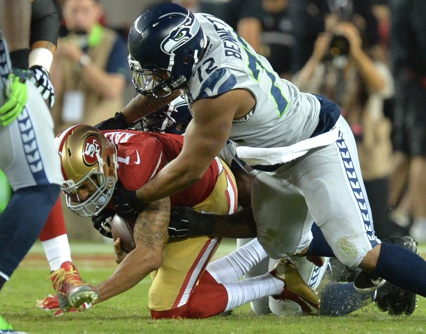 From left, San Francisco 49ers quarterback Colin Kaepernick (7), gets sacked by Seattle Seahawks defensive end Michael Bennett (72) and Seattle Seahawks defensive end Cliff Avril (56) in the second quarter of their NFL game at Levi's Stadium in Santa Clara, Calif., on Thursday, Oct. 22, 2015. (Doug Duran/Bay Area News Group)