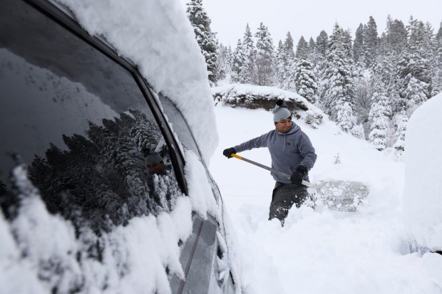 Fernando Cori digs out his families buried cars on Donner Pass Road near Donner Summit after the first in a series of storms dumped about a foot of snow in the Sierras and about 5 inches around Lake Tahoe Wednesday March 14, 2017. Forecasters are calling for an additional 2-3 feet from a stronger storm Thursday through Saturday.
