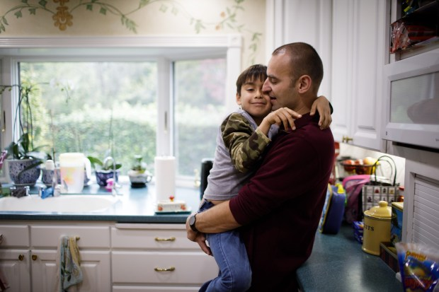 Tomasz Kruczek, hugs his son, Gabriel, 8, at their Fremont home on March 21, 2018. Tomasz Kruczek and his wife are worried that their eight-year-old son, Gabriel, is having a hard time adjusting since the family moved. (Dai Sugano/Bay Area News Group)
