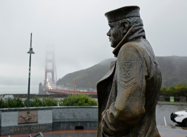 The statue of the Lone Sailor, near the Golden Gate Bridge, looks out at a passing rain storm Tuesday, Jan. 5, 2016, in Sausalito, Calif. A group in San Jose is raising funds for a Lone Sailor statue to be erected in Guam. (AP Photo/Eric Risberg)