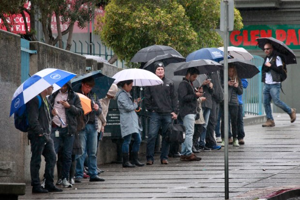 """Bay Area morning commuters brace themselves for the """"atmospheric river"""" rolling into the state, Tuesday, March 20, 2018, in San Francisco, Calif., (Karl Mondon/Bay Area News Group)"""