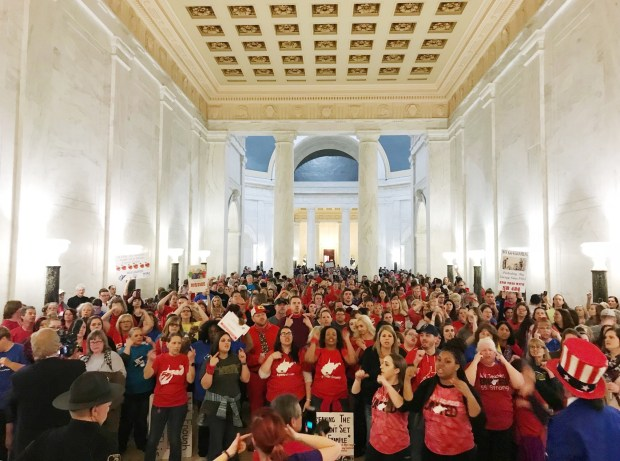 Teachers celebrate after West Virginia Gov. Jim Justice and Senate Republicans announced they reached a tentative deal to end a statewide teachers' strike by giving them 5 percent raises in Charleston, W.Va., Tuesday, March 6, 2018. (AP Photo/Robert Ray)