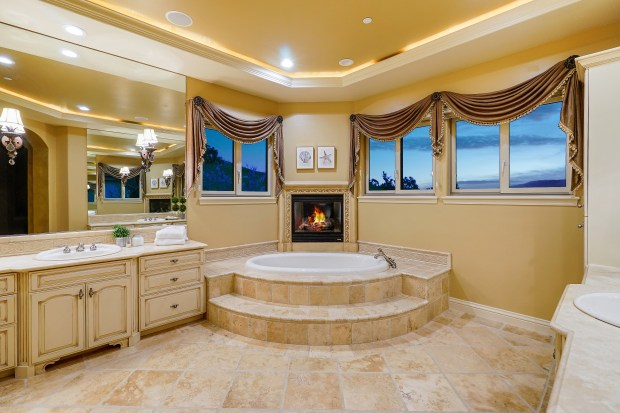 In the master bathroom with travertine tile flooring, relax in a step-up soaking tub as the gas fireplace creates a soothing atmosphere.