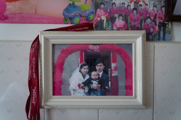 A photo of Liu Hua and Sreynich Yorn holding their son at their weddingceremony in early 2015 is hung on the wall in their house in Leping, China. MUST CREDIT: Photo for The Washington Post by Yan Cong