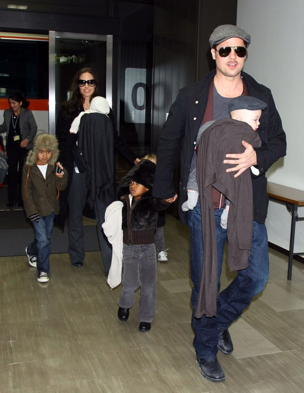 """NARITA, JAPAN - JANUARY 27: Actor Brad Pitt and Angelina Jolie arrive at Narita International Airport with their children (L to R) Maddox, Vivienne, Zahara and Knox on January 27, 2009 in Narita, Chiba, Japan. Brad is visiting Japan to promote his film """"The Curious Case Of Benjamin Button"""". (Photo by Junko Kimura/Getty Images)"""