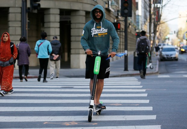San Jose State student Harman Ghotra, 21, picks up a Lime-S electric scooter to get to campus faster to turn in a paper in San Jose, Calif., on Tuesday, April 3, 2018. Bike and scooter-sharing companies are flooding San Jose and other Bay Area cities with dock-less bikes and scooters, including electric ones. (Laura A. Oda/Bay Area News Group)