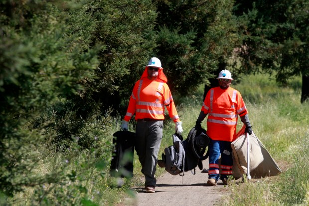 Caltrans employees David Lopez and Jorge Chavez collect trash during a roadside clean-up on the onramp from the Almaden Expressway to Highway 85 in San Jose, Calif., Thursday, April 19, 2018. (Karl Mondon/Bay Area News Group)