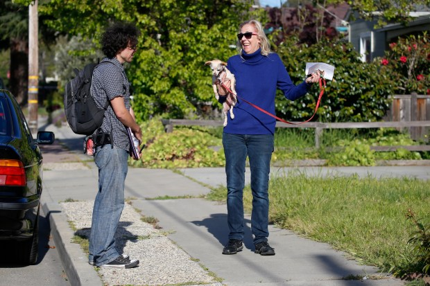 Zav Hershfield, at left, talks to Anita Grunwald, holding her dog, Sandie, as he canvasses the Seabright neighborhood while looking for residents to sign a rent control ballot measure on Friday, April 20, 2018, in Santa Cruz, Calif. (Jim Gensheimer/Special to Bay Area News Group)