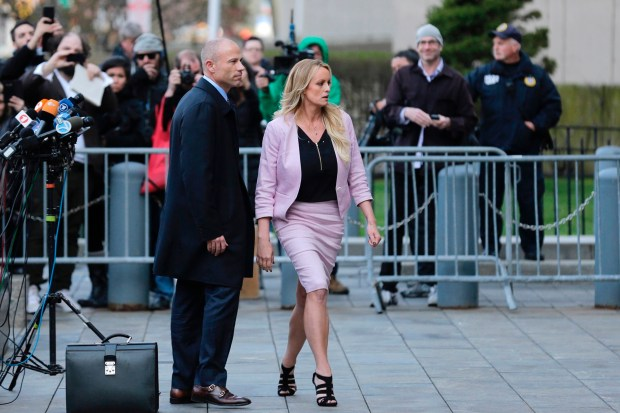 Porn actress Stormy Daniels, accompanied by her attorney, Michael Avenatti, left, leaves federal court, Monday, April 16, 2018 in New York. A U.S. judge listened to more arguments about President Donald Trump's extraordinary request that he be allowed to review records seized from his lawyer, Michael Cohen, office as part of a criminal investigation before they are examined by prosecutors. The raid carried out last Monday at Cohen's apartment, hotel room, office and safety deposit box sought bank records, records on Cohen's dealing in the taxi industry, Cohen's communications with the Trump campaign and information on payments made in 2016 to former Playboy model Karen McDougal and to Daniels. (AP Photo/Seth Wenig)