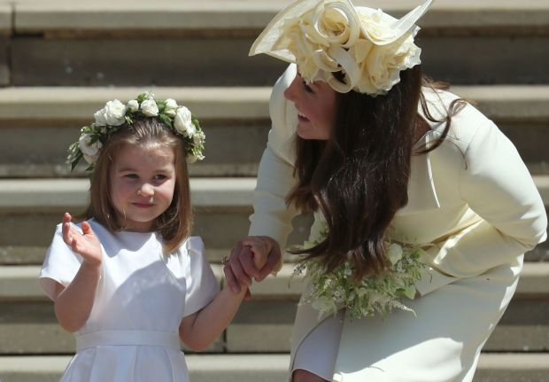 TOPSHOT - Princess Charlotte (L) waves by her mother Britain's Catherine, Duchess of Cambridge after attending the wedding ceremony of Britain's Prince Harry, Duke of Sussex and US actress Meghan Markle at St George's Chapel, Windsor Castle, in Windsor, on May 19, 2018. / AFP PHOTO / POOL / Jane BarlowJANE BARLOW/AFP/Getty Images