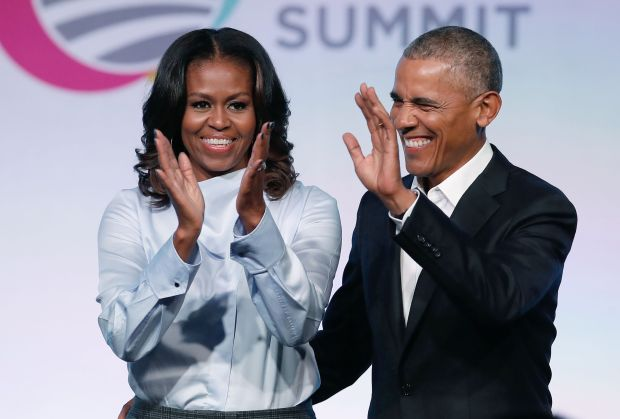 (FILES) In this file photo taken on October 31, 2017, former US President Barack Obama and First Lady Michelle Obama arrive at the Obama Foundation Summit in Chicago, Illinois.Barack and Michelle Obama have entered into a multi-year agreement to produce films and series with Netflix, the world's leading internet entertainment service announced on May 21, 2018. The former first couple have launched Higher Ground Productions to produce a variety of content for the video streamer, possibly including scripted series, documentaries and features. / AFP PHOTO / Jim YoungJIM YOUNG/AFP/Getty Images