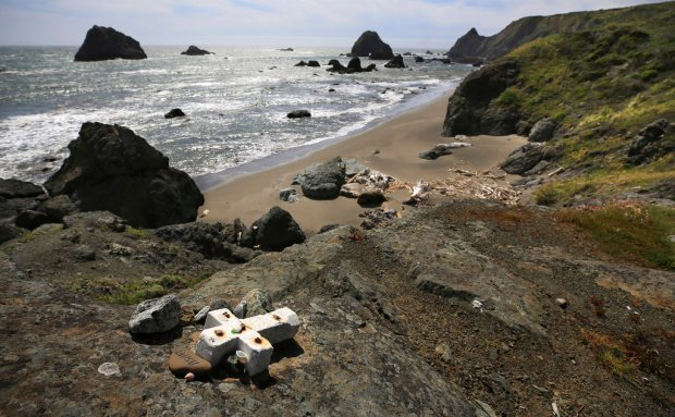 In this May 5, 2017 file photo, a memorial cross of stone for Lindsay Cutshall and her fiance, Jason Allen is bolted to a cliff above Fish Head Beach in honor of the two who were found murdered in 2004 just north of Jenner, Calif. A Northern California man has been charged with killing the Midwestern couple as they slept on the remote beach more than a decade ago. Authorities said Wednesday, May 16, 2018, Shaun Gallon, of Forestville, was charged last week with two counts of murder. Prosecutors say Gallon used a rifle to shoot Cutshall, of Ohio, and Allen, of Michigan, as they lay in sleeping bags on Fish Head Beach in Jenner in August of 2004. (Kent Porter /The Press Democrat via AP, File)