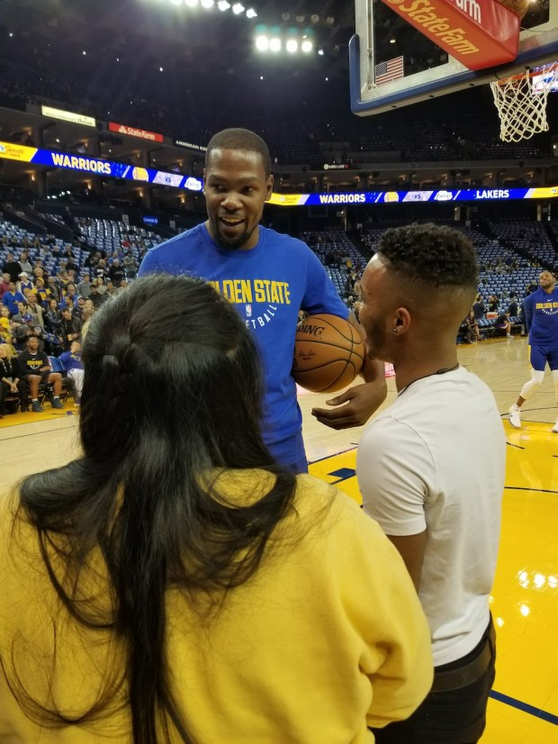 Golden State Wariors' Kevin Durant catches up with Dez Frazier and Yaritza Rodriguez after spotting them in the stands at a Warriors game on Dec. 22, 2017.(Courtesy of Shannon Petrello)