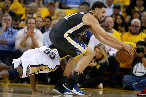 Golden State Warriors' Klay Thompson (11) goes for the loose ball against New Orleans Pelicans' E'Twaun Moore (55) in the first quarter of Game 2 of the NBA Western Conference semifinals at Oracle Arena in Oakland, Calif., on Tuesday, May 1, 2018. (Nhat V. Meyer/Bay Area News Group)