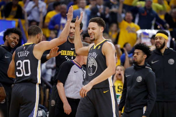Golden State Warriors' Stephen Curry (30) and Klay Thompson (11) celebrate in the first quarter of Game 4 of the NBA Western Conference finals against the Houston Rockets at Oracle Arena in Oakland, Calif., on Tuesday, May 22, 2018. (Nhat V. Meyer/Bay Area News Group)