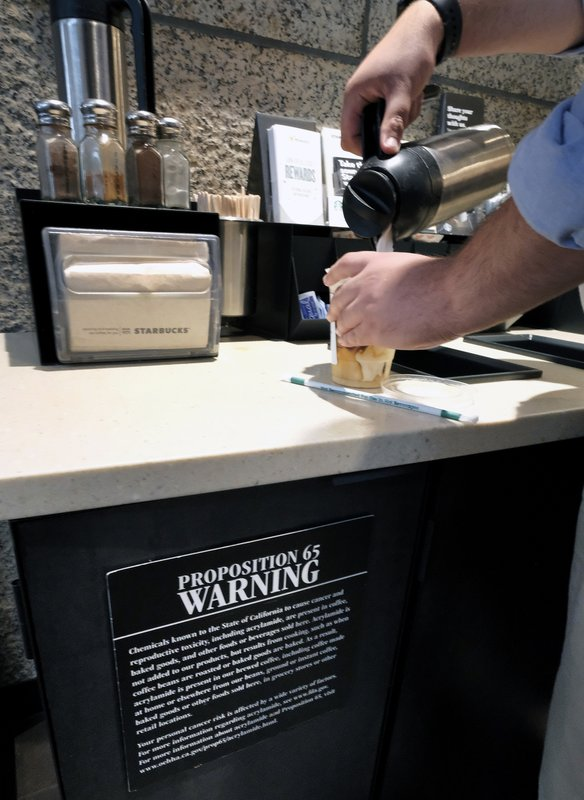 As customer pours milk into coffee near a posted Proposition 65 warning sign at a Starbucks coffee shop in Los Angeles. (AP Photo/Richard Vogel, File)