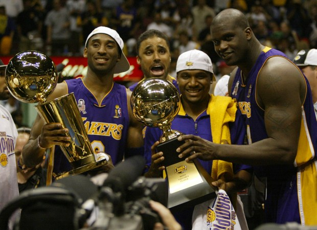 Los Angeles Lakers Kobe Bryant, left, holding the championship trophy, celebrates with teammates Rick Fox, Lindsey Hunter, second from right, and Shaquille O'Neal, right, holding the MVP trophy, after winning Game 4 of the NBA Finals, Wednesday, June 12, 2002, in East Rutherford, N.J. The Lakers defeated the New Jersey Nets 113-107, capturing their third consecutive NBA championship. (AP Photo/Michael Conroy)