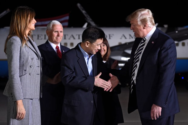 US President Donald Trump (R) shakes hands with US detainee Tony Kim (C) as US Vice President Mike Pence (back L) and Melania Trump (L) look on, upon arrival after three detainees were freed by North Korea, at Joint Base Andrews in Maryland on May 10, 2018. - US President Donald Trump greeted the three US citizens released by North Korea at the air base near Washington early on May 10, underscoring a much needed diplomatic win and a stepping stone to a historic summit with Kim Jong Un. (Photo by SAUL LOEB / AFP) (Photo credit should read SAUL LOEB/AFP/Getty Images)